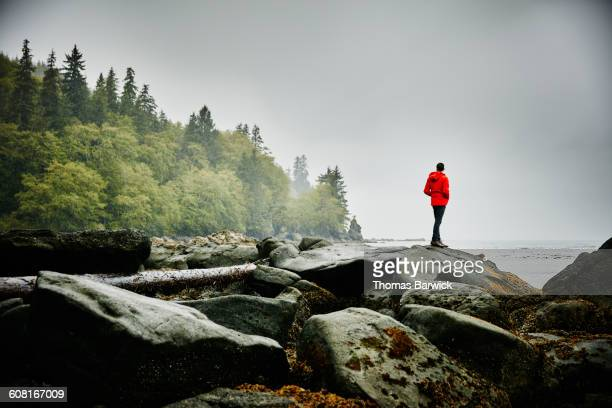 Man standing on boulders on shoreline of ocean