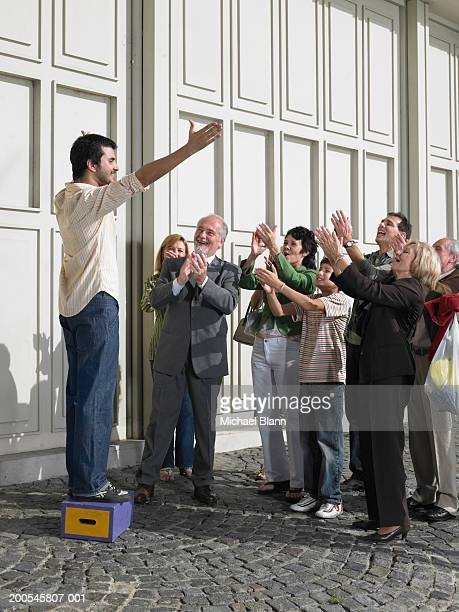 man standing on box in street holding out arms to applauding crowd - surrounding stock pictures, royalty-free photos & images