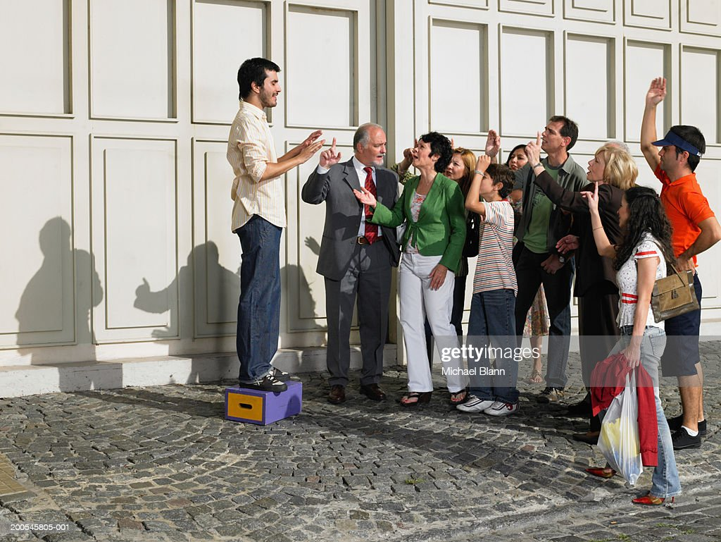 Man standing on box in street speaking to crowd raising hands : Stock Photo