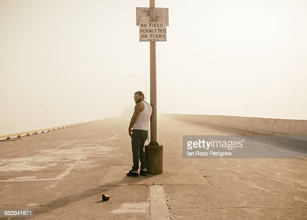 Man standing on break wall by shore