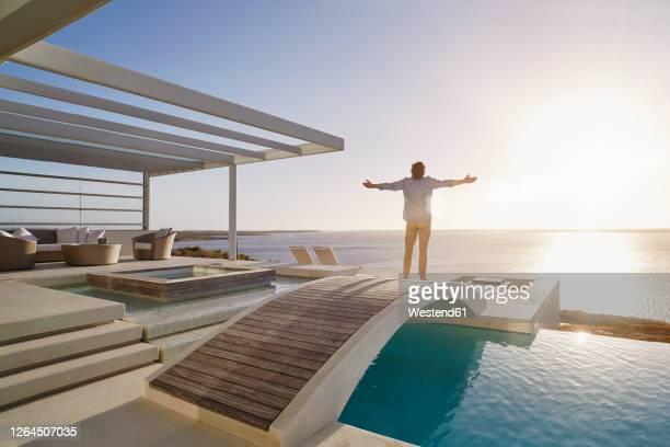 man standing on bridge above a swimming pool enjoying the view - ein mann allein stock-fotos und bilder
