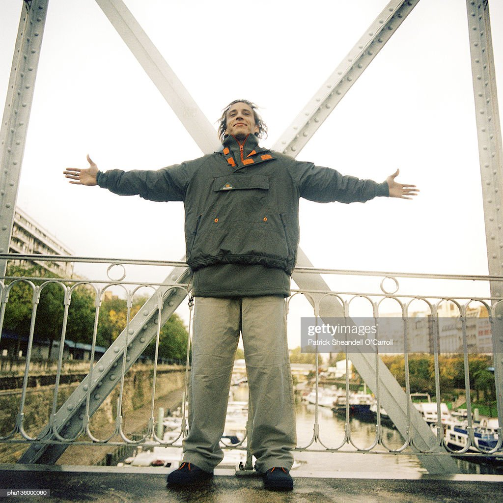 Man standing on bridge wearing winter clothes with arms stretched out : Stockfoto