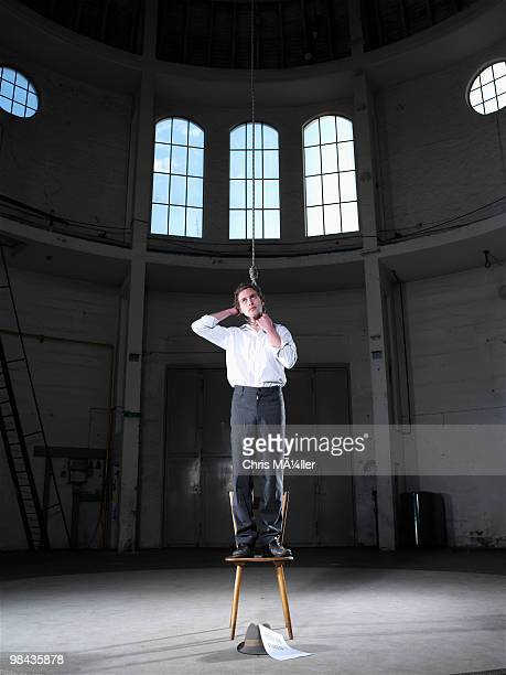 man standing on chair in empty building ready to hang himself - hanging death photos stock pictures, royalty-free photos & images