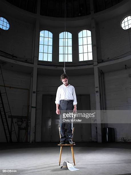 man standing on chair in empty building ready to hang himself - suicidio fotografías e imágenes de stock