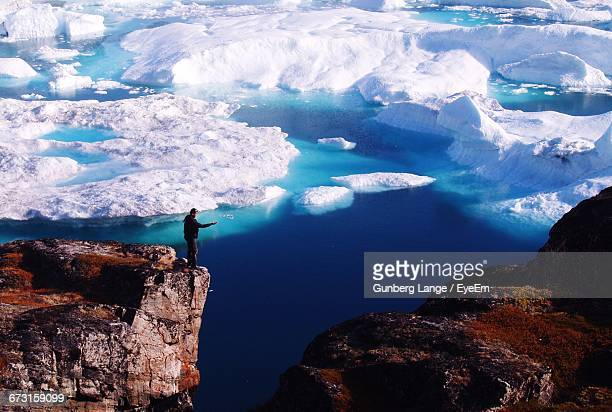 Man Standing On Cliff Against Icebergs In Sea