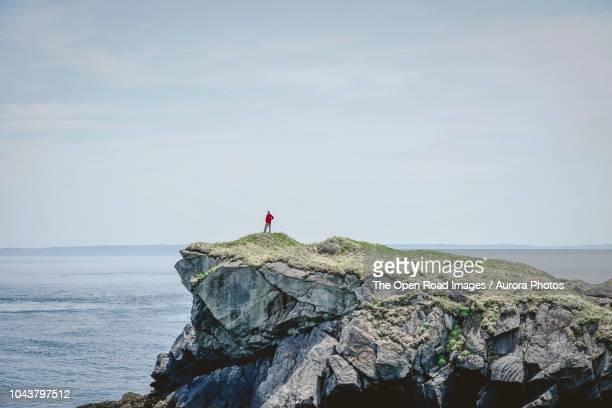 man standing on cliff and looking at ocean - klippe stock-fotos und bilder