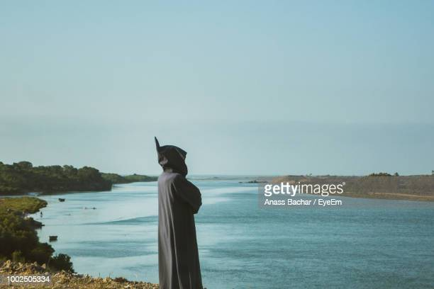 Man Standing On Cliff By Sea Against Clear Sky