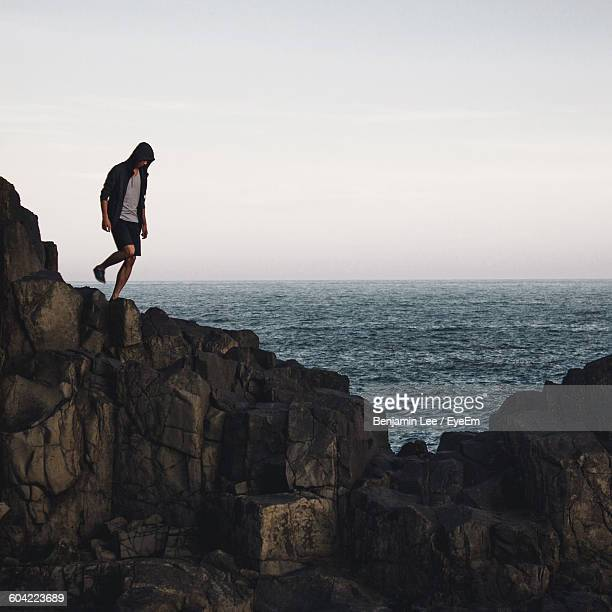 Man Standing On Cliff By Sea Against Sky