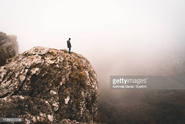 man standing on cliff during foggy weather - david cliff stock pictures, royalty-free photos & images