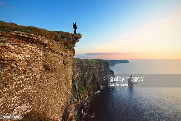 Man standing on cliff edge, Cliffs of Moher