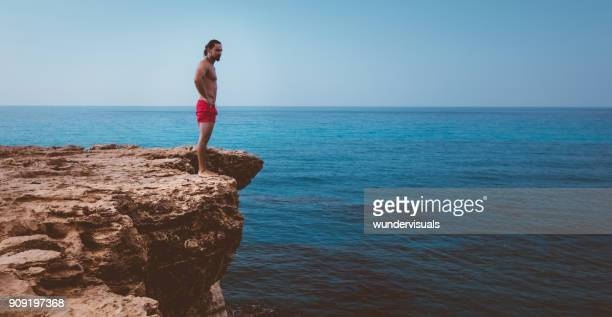 Man standing on cliff edge ready to jump into sea