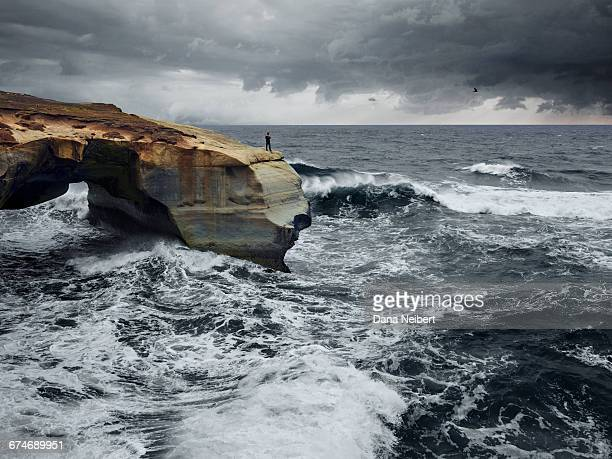Man standing on cliff with storm