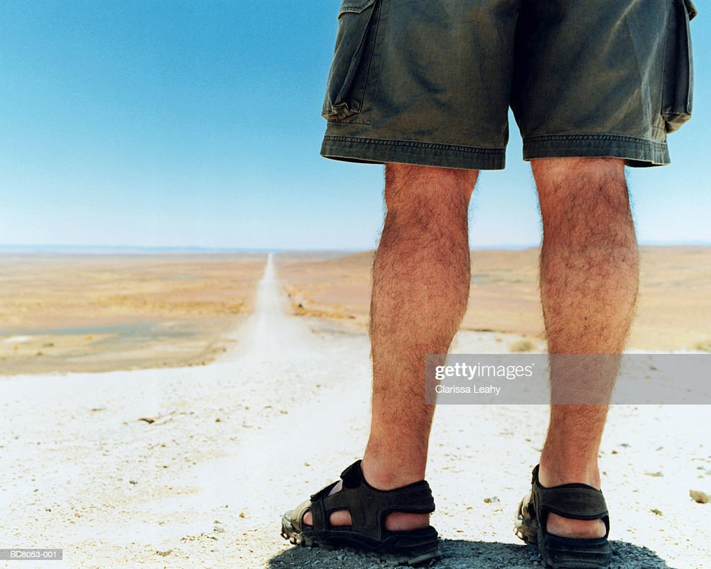 Man standing on country road, rear view (low-section) : Stock Photo