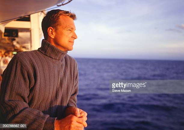 man standing on cruise ship deck looking out to sea - railings stock pictures, royalty-free photos & images