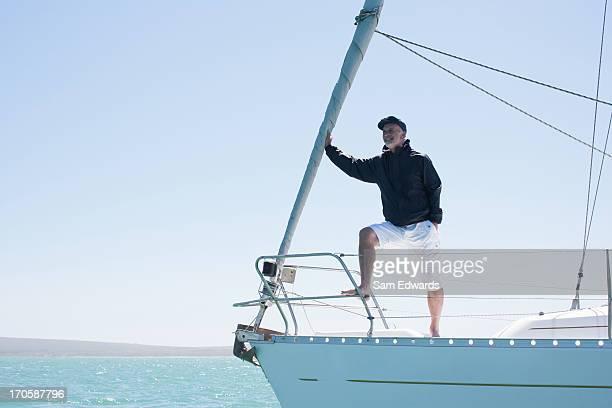 Homme debout sur le pont du bateau à voile