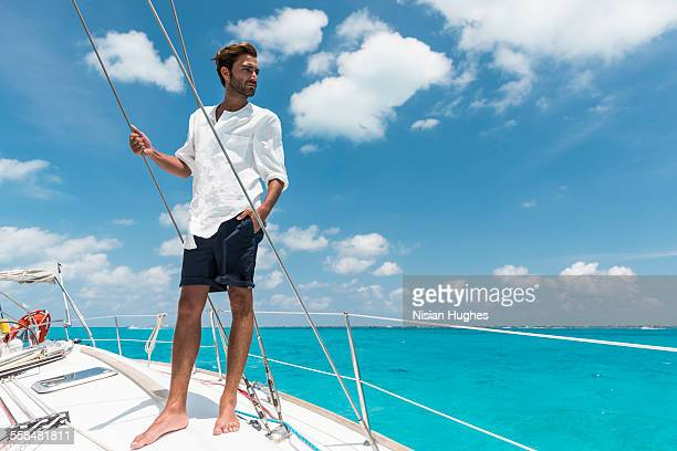 man standing on deck of sailboat