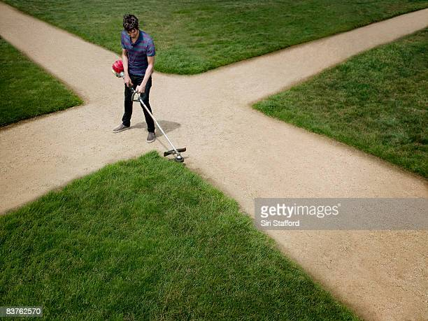 Man standing on dirt crossroad trimming lawn