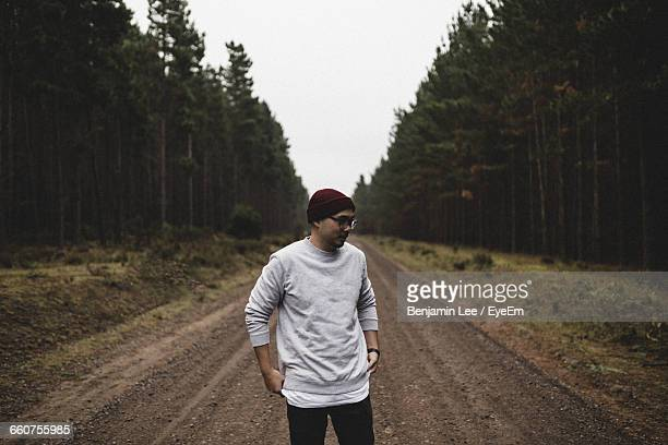 Man Standing On Dirt Road In Forest Against Clear Sky