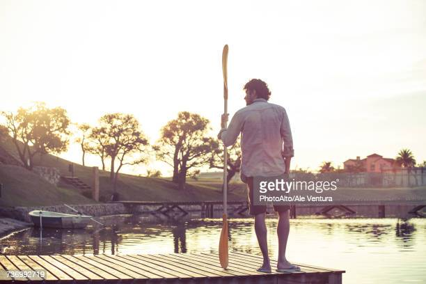 Man standing on dock with oar in hand