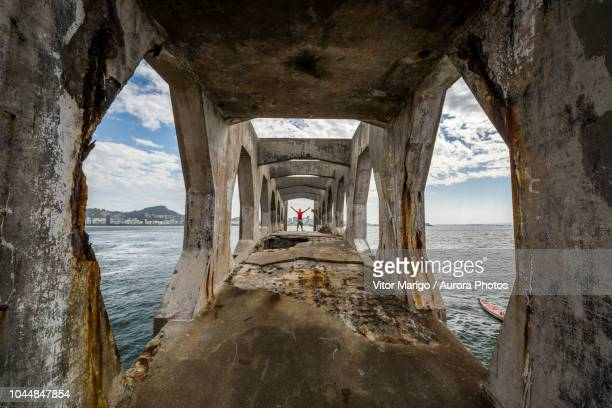 man standing on edge of abandoned structure in laje fort in guanabara bay, rio de janeiro, brazil - laje stock pictures, royalty-free photos & images
