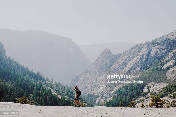 man standing on field against mountains in foggy weather - yosemite nationalpark stock pictures, royalty-free photos & images