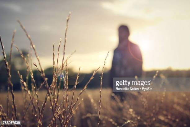 Man Standing On Field Against Sky During Sunset