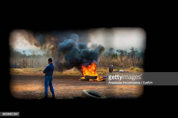 Man Standing On Field While Tire Burning In Background