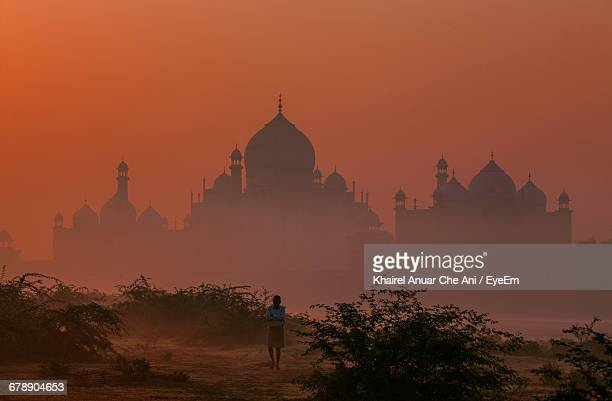 Man Standing On Field With Silhouette Taj Mahal In Background During Sunrise