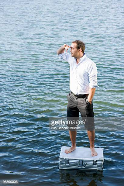 man standing on floating suitcase