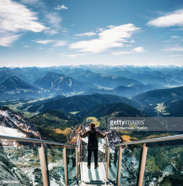 man standing on footbridge over mountains against sky - salzburg stock pictures, royalty-free photos & images