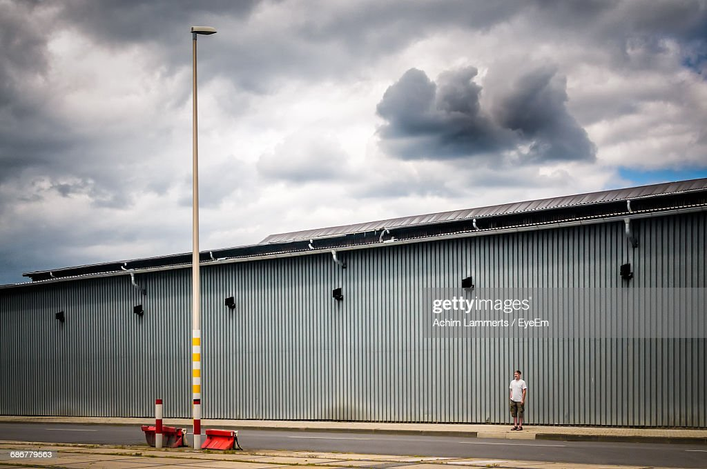 Man Standing On Footpath By Factory Against Cloudy Sky : Stock-Foto