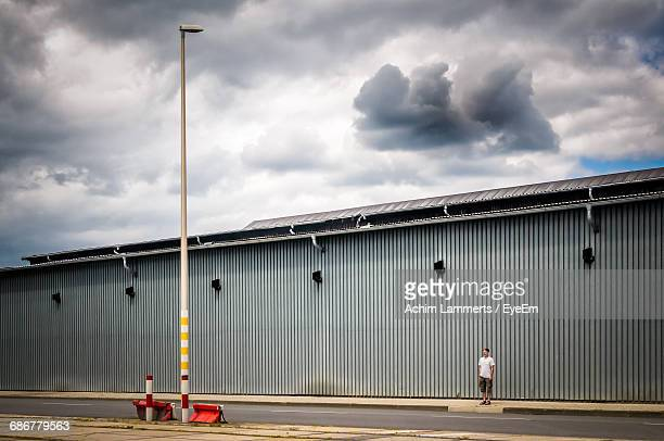 man standing on footpath by factory against cloudy sky - achim lammerts fotografías e imágenes de stock