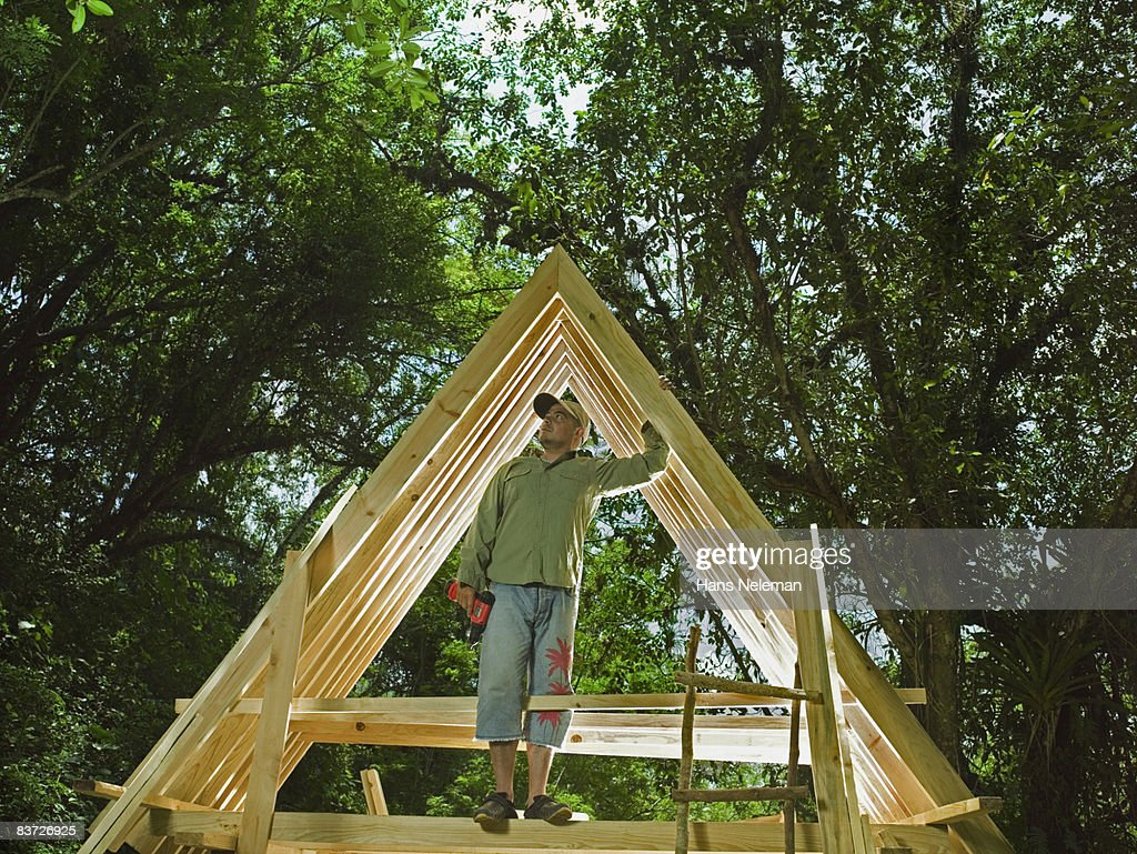 Man standing on frame of house in forest : Stock Photo