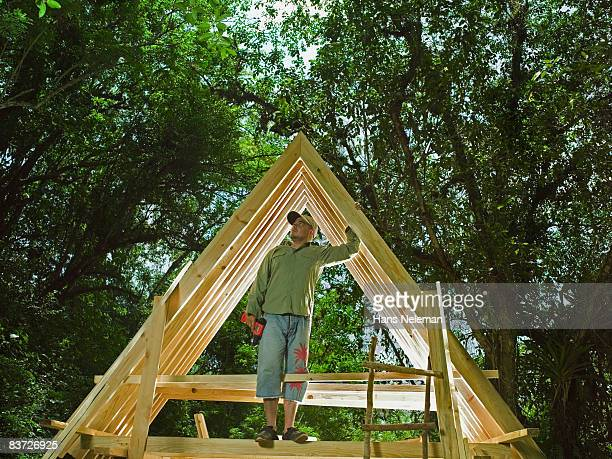 Man standing on frame of house in forest