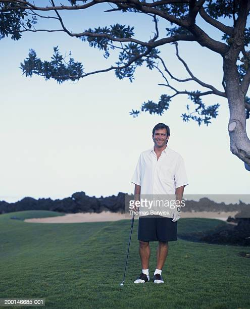 Man standing on golf course, holding golf club, portrait