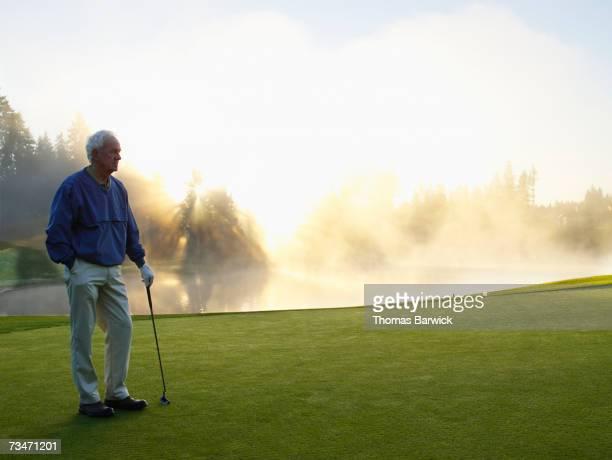 man standing on golf course, holding golf club, side view - só um homem idoso - fotografias e filmes do acervo