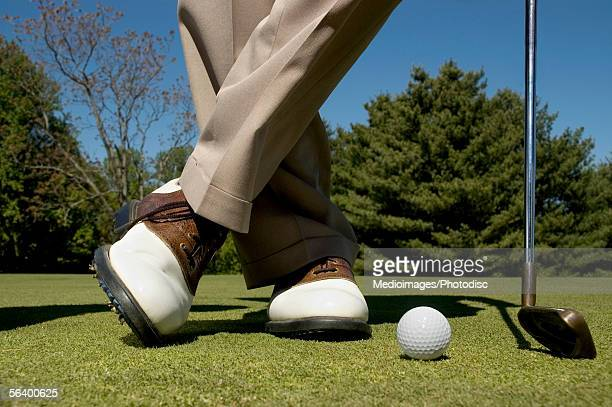 Man standing on golf course with iron and golf ball