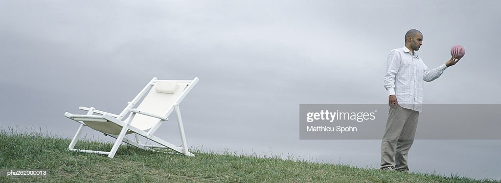 Man standing on grass near lounge chair holding ball in hand : Stockfoto
