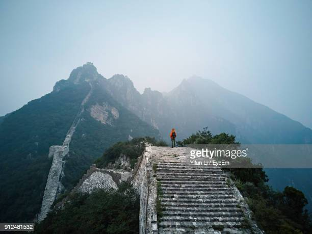 man standing on great wall of china by mountain against clear sky - beijing province stock photos and pictures