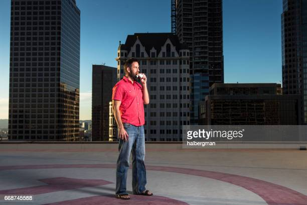 Man Standing on Heliport Eating Burrito