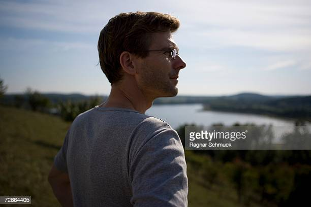 Man standing on hill and looking at view