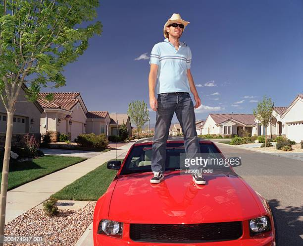 Man standing on hood of red car