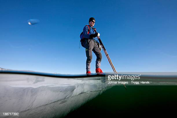 Man standing on ice with pole