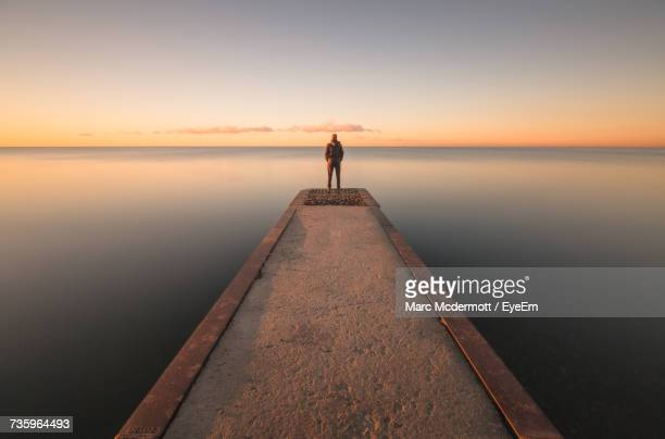 man standing on jetty against sky during sunset - symmetry stock pictures, royalty-free photos & images