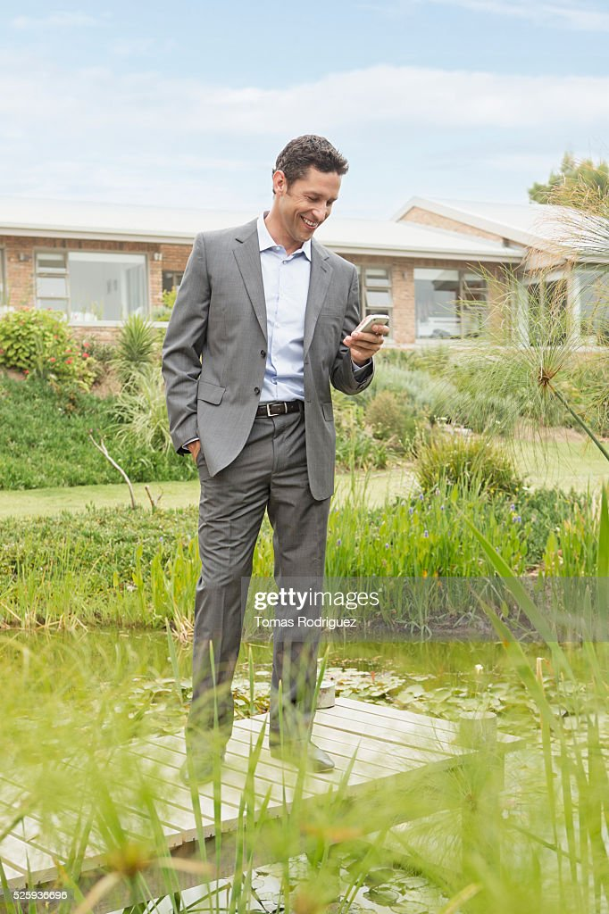 Man standing on jetty by pond in back yard and text messaging : Stock-Foto