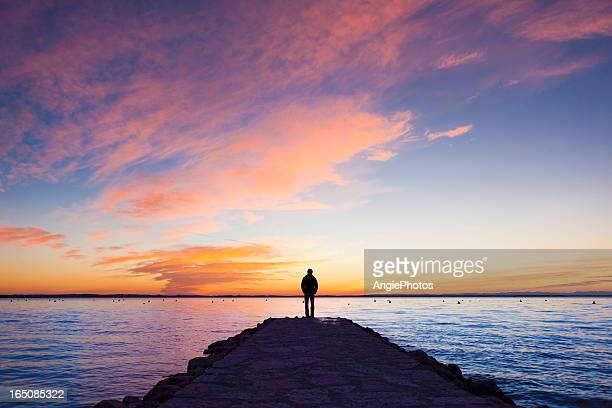 man standing on jetty - sunset lake stock photos and pictures