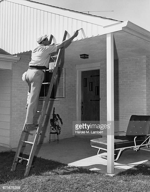 man standing on ladder and painting roof  - {{relatedsearchurl(carousel.phrase)}} ストックフォトと画像