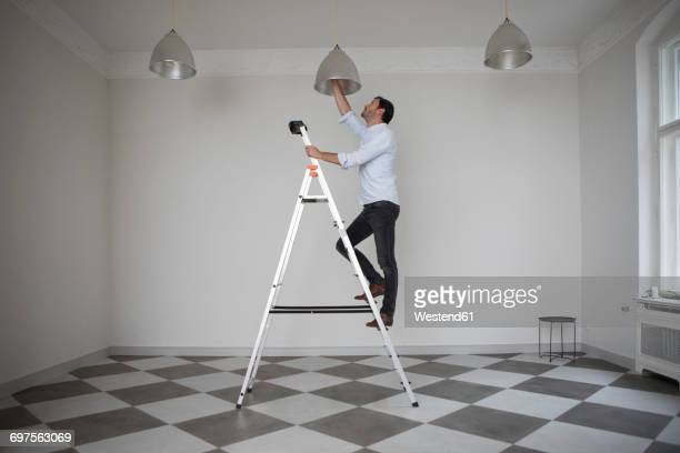 Man standing on ladder in an empty room changing bulb of ceiling light