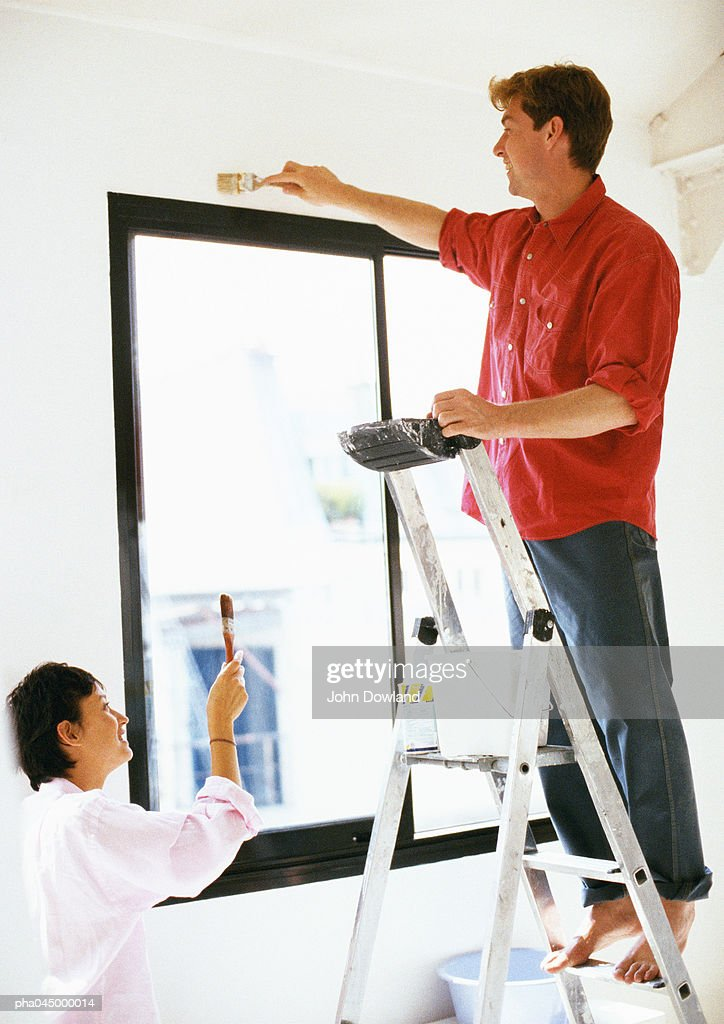 Man standing on ladder, painting wall, woman holding up brush : Stockfoto