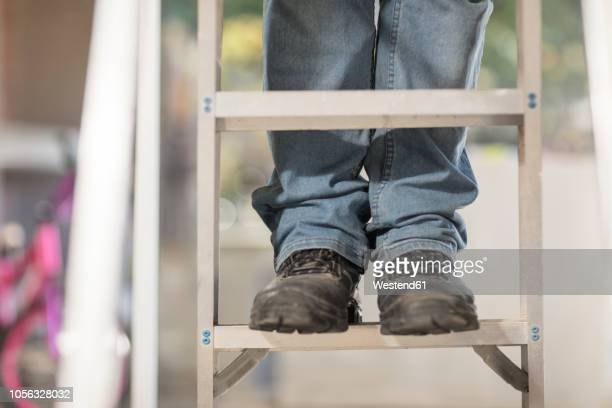 man standing on ladder, partial view - step ladder stock photos and pictures